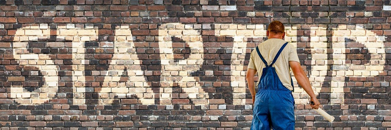 A man standing in front of a brick wall